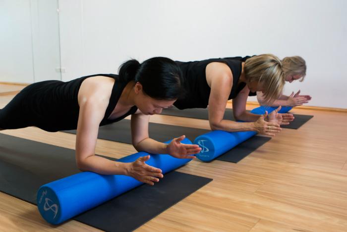 Women in dynamic pilates class foam roller YHP